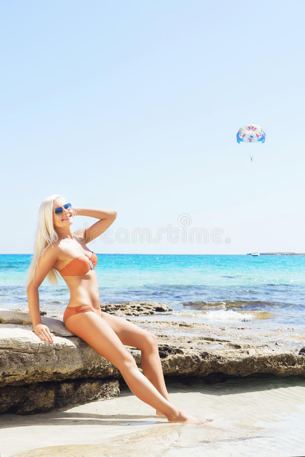 比基尼泳装的年轻和性感的妇女在海滩 免版税库存图片