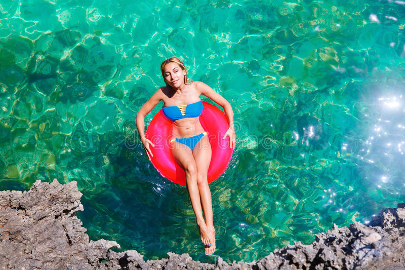 比基尼泳装的年轻美丽的女孩在rubb的热带海游泳 免版税库存图片