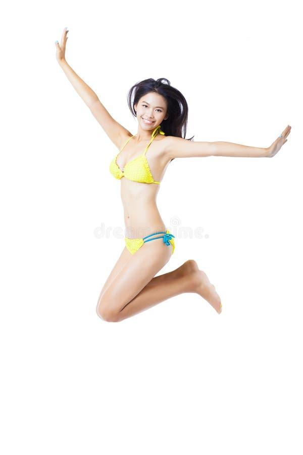 比基尼泳装跳跃的少妇 免版税库存图片