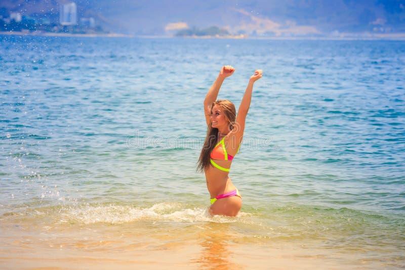 比基尼泳装蹲坐的白肤金发的亭亭玉立的体操运动员在天蓝色的海微笑 免版税库存照片
