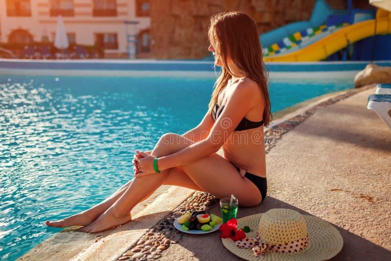 比基尼泳装饮用的鸡尾酒和吃果子的妇女由游泳场 所有包含 ?? 库存照片