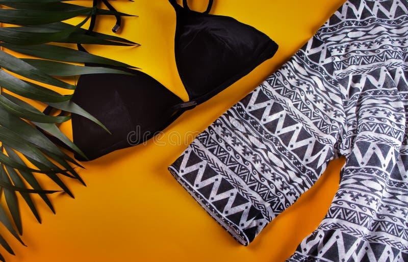 比基尼泳装黑色天鹅绒泳装、海滩海角和热带棕榈叶在黄色背景 妇女的游泳衣顶上的看法  图库摄影