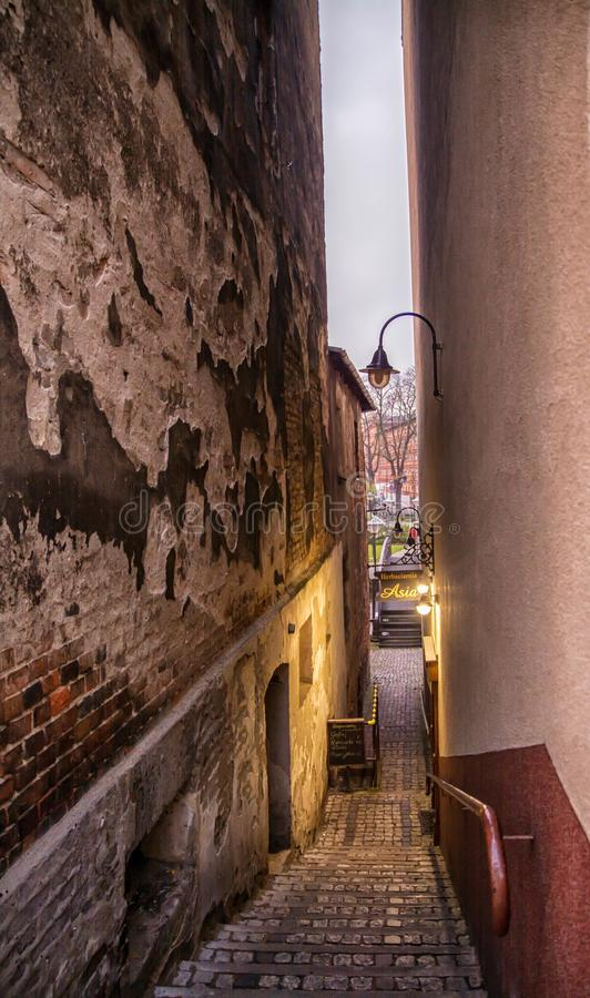 比得哥什,波兰,老历史经济公寓住宅五颜六色的门面  非常狭窄的街道和灯在台阶点燃 库存图片