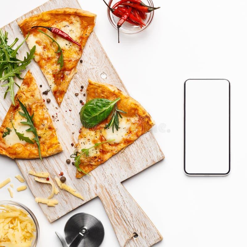 比萨切片和智能手机有黑屏的 免版税库存照片