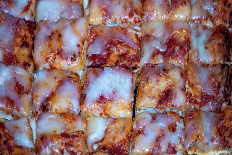 比萨切片被削减成小叮咬,面团用fanina酵母做了,并且水、一个小的蕃茄和无盐干酪使任何人愉快 免版税库存图片