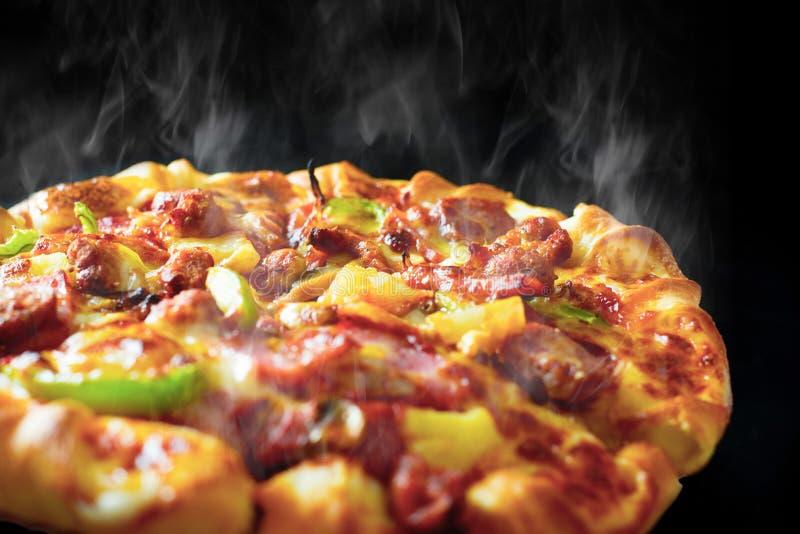 比萨用乳酪火腿烟肉和意大利辣味香肠在被隔绝的黑背景与热的通入蒸汽的烟 食物和烹调概念 ?? 免版税库存照片