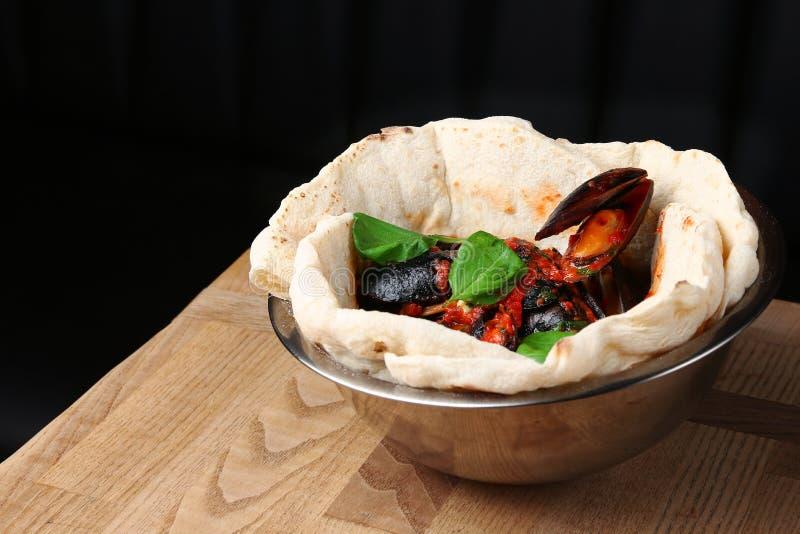 比萨用在桌餐馆传统比萨的淡菜与蓬蒿叶子 库存照片