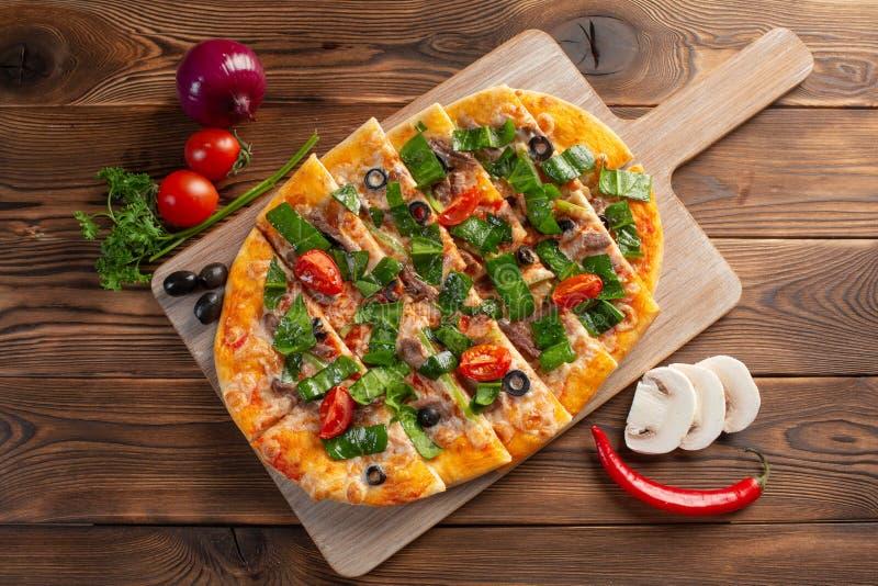 比萨用小牛肉和干蕃茄在木背景 库存照片