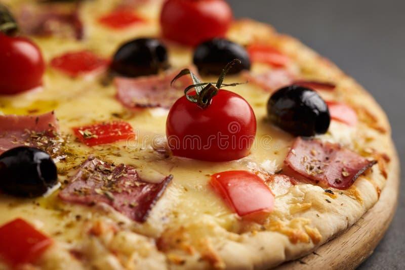 比萨用火腿、无盐干酪乳酪、西红柿、红辣椒、黑橄榄和牛至 家做了食物 鲜美的概念和 库存图片