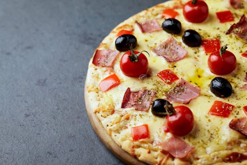 比萨用火腿、无盐干酪乳酪、西红柿、红辣椒、黑橄榄和牛至 家做了食物 鲜美的概念和 库存照片