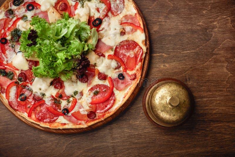 比萨用火腿、蒜味咸腊肠、乳酪、蘑菇、西红柿、甜椒和沙拉在一个木棕色委员会 库存图片