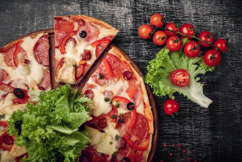 比萨用火腿、蒜味咸腊肠、乳酪、蘑菇、西红柿、甜椒和沙拉在黑粉笔板 免版税库存照片