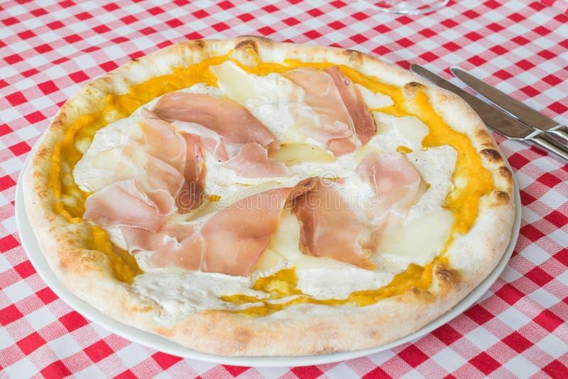 比萨用火腿和乳酪在桌上在意大利餐厅,午饭时间 免版税库存图片
