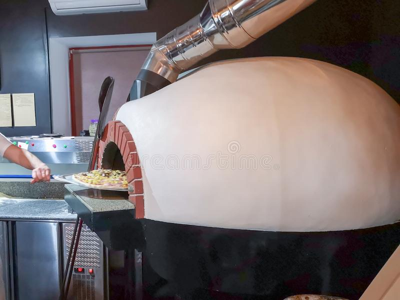 比萨的,侧视图烤箱 餐馆厨师在传统餐馆采取从烤箱的比萨 免版税库存照片