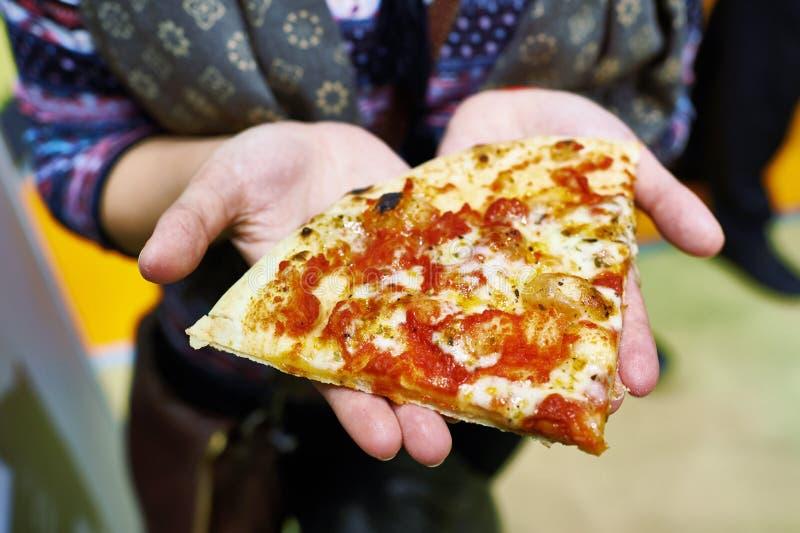比萨饼在妇女的手上 图库摄影