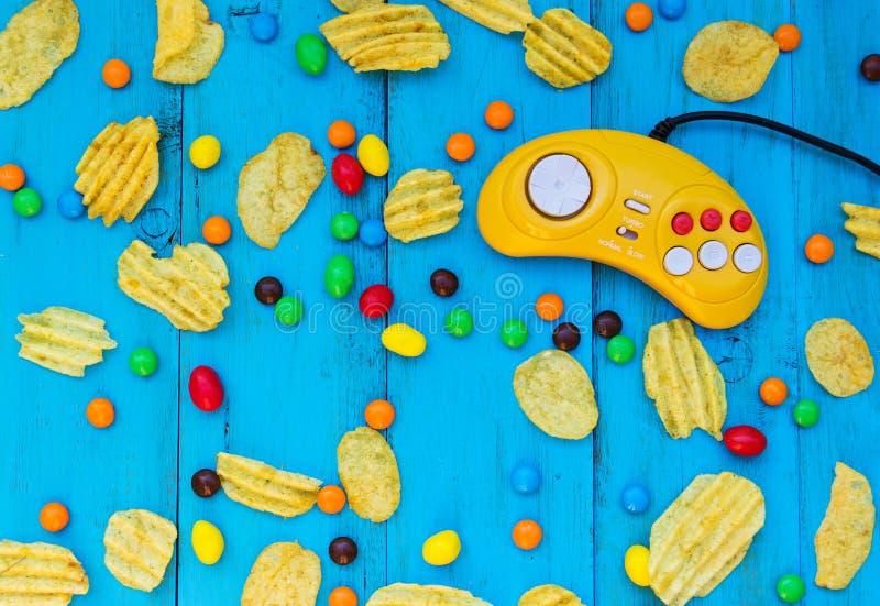 比赛控制器、芯片和糖果在蓝色木背景 库存照片