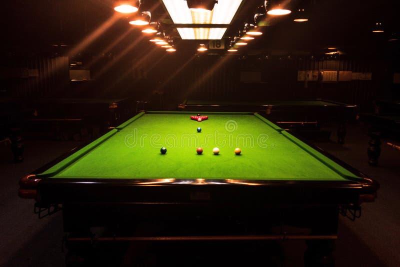 比赛竞争落袋撞球球、桌和橙色光 免版税库存图片