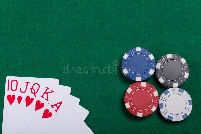 比赛芯片和卡片在绿色啤牌桌上 在同花大顺啤牌的一个赢取的组合 库存图片