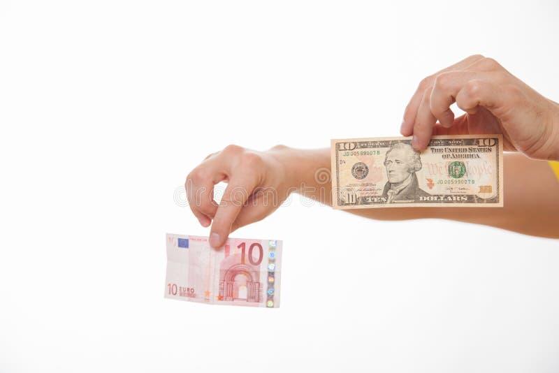 比较两张钞票的男性手-欧元和美元 免版税库存照片