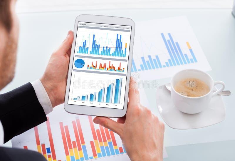 比较在数字式片剂的商人图表在书桌 库存图片