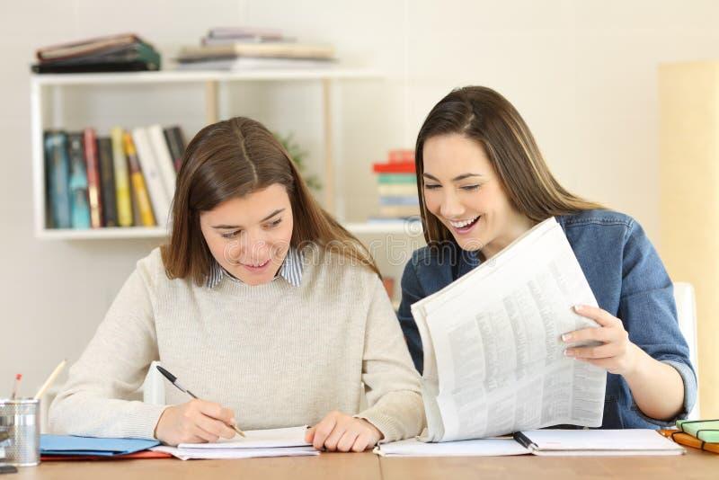 比较报纸新闻的两名学生 免版税库存照片