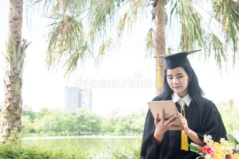 毕业使用平板电脑的美女 毕业生亚洲女学生佩带的毕业帽子和褂子,背景是自然  库存图片