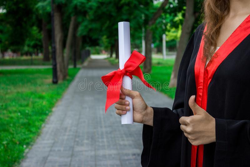 毕业生在她的手举起她的手和庆祝与证明和如此感觉幸福在开业日 免版税库存照片