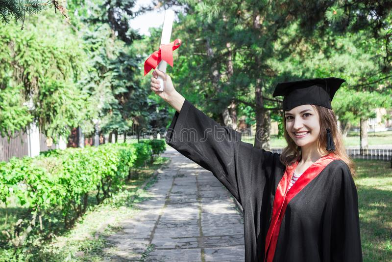 毕业生在她的手举起她的手和庆祝与证明和如此感觉幸福在开业日 免版税图库摄影