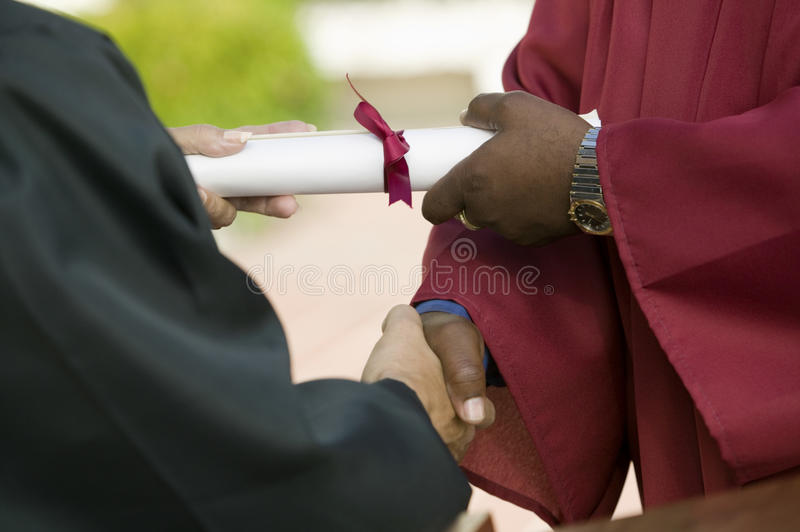 毕业生接受文凭和握手中间部分 免版税库存照片