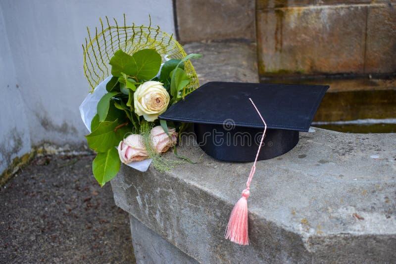 毕业盖帽或mortaboard与一束玫瑰在老台阶在毕业典礼举行日 库存照片