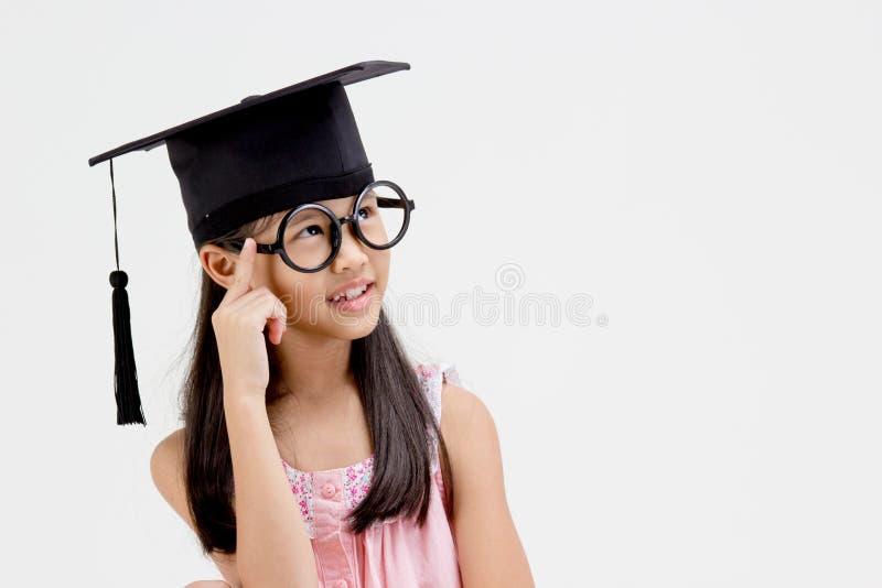 毕业盖帽的愉快的亚裔学校孩子毕业生 免版税图库摄影