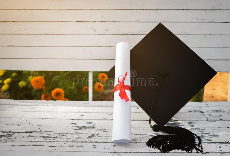 毕业盖帽,有程度纸的帽子在白色木桌,摘要上 库存图片