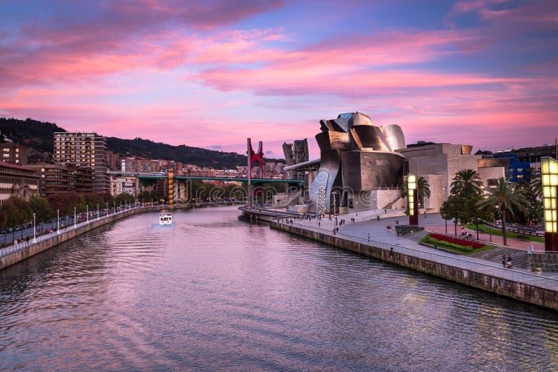 毕尔巴鄂古根海姆美术馆、Nervion河和La药膏桥梁在桃红色日落在毕尔巴鄂,西班牙 图库摄影