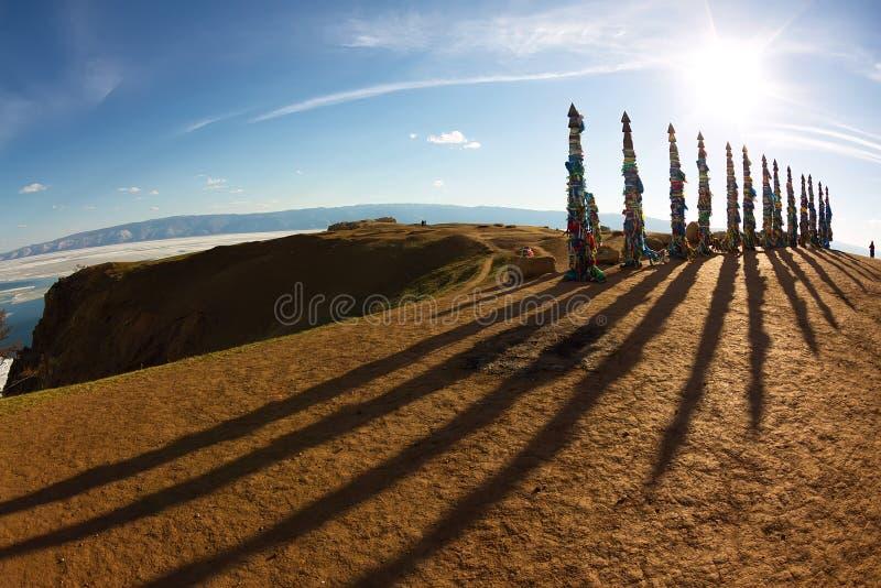 毛哔叽僧人杆在Olkhon的在与长的阴影的日落 库存照片