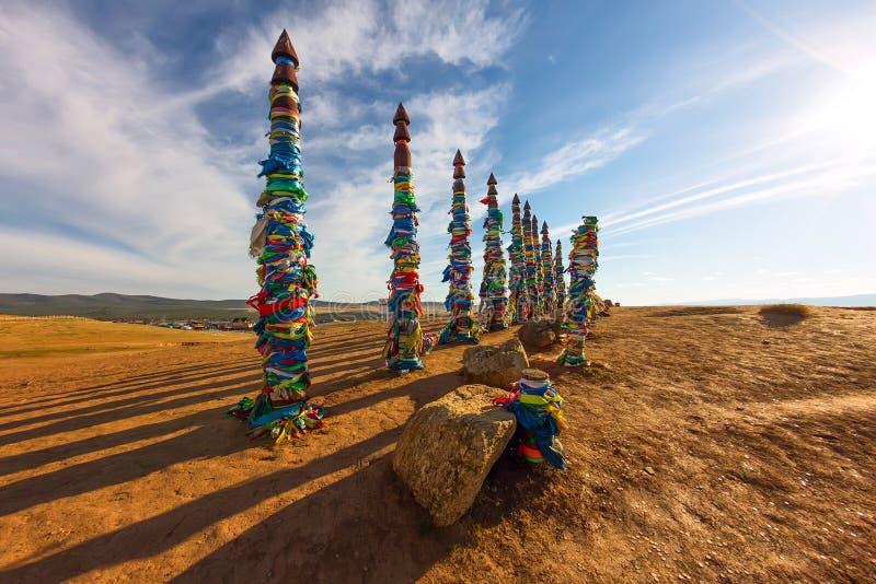 毛哔叽僧人杆在Olkhon的在与长的阴影的日落 图库摄影