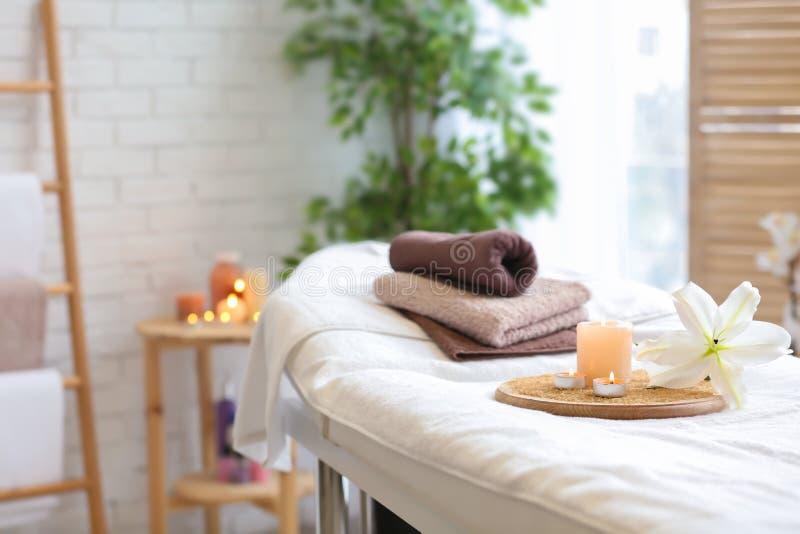 毛巾、蜡烛和花在按摩桌上 库存照片