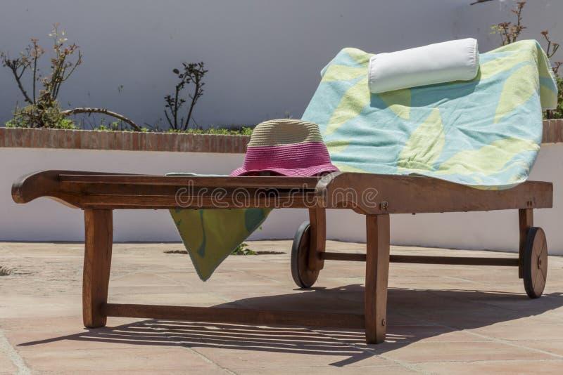 毛巾和帽子占领的木太阳可躺式椅 在度假 免版税库存照片