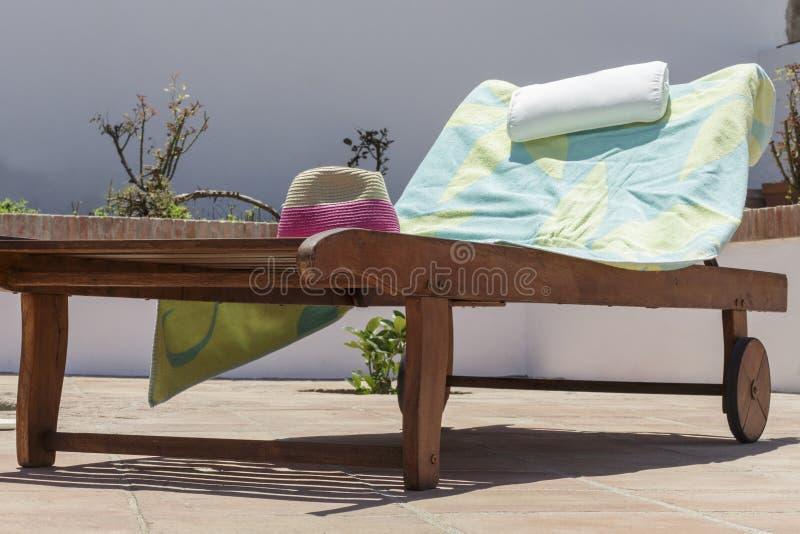 毛巾和帽子占领的木太阳可躺式椅 在度假 图库摄影