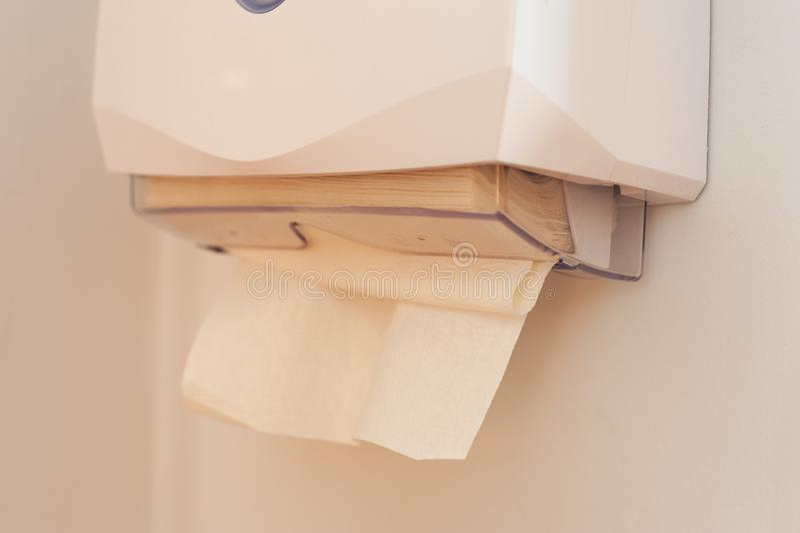 毛巾纸特写镜头在垂悬在墙壁上的分配器的 免版税图库摄影