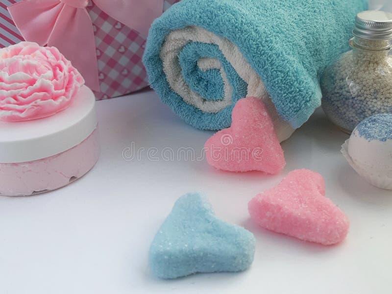 毛巾,肥皂,奶油瓶子,洗刷心脏形状在白色背景的 图库摄影