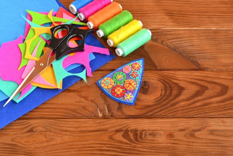 从毛毡小块,节约工艺的手工制造别针 剪刀,毛毡片断 与拷贝空间的木背景文本的 库存照片