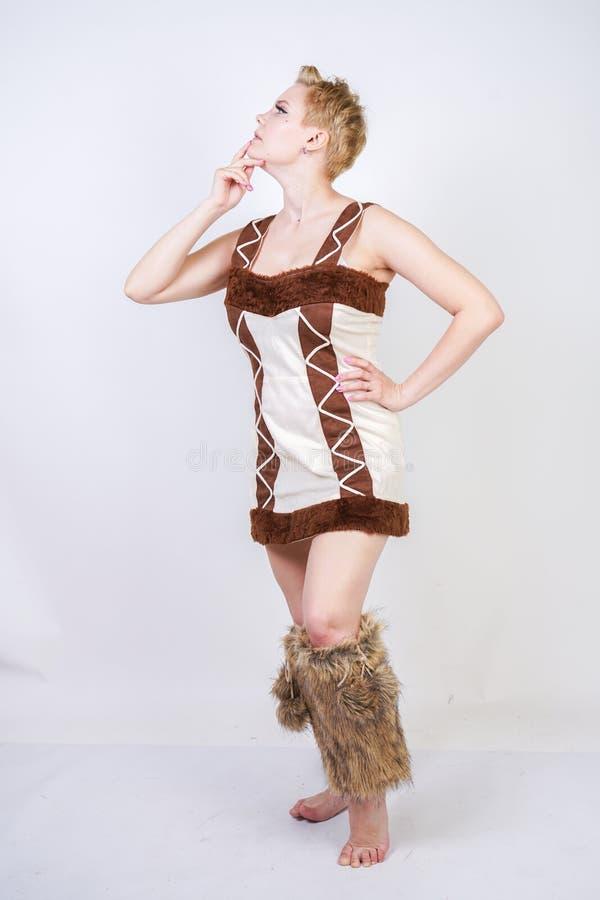 毛皮原始人狂欢节服装的热的正大小妇女白色背景的在演播室 一棕色dre的一个美丽的野蛮女孩 图库摄影