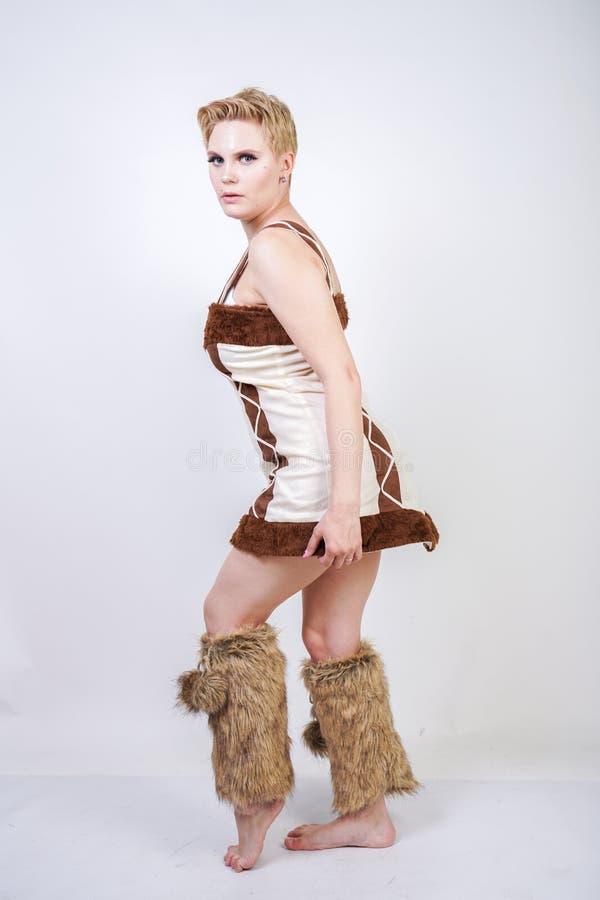 毛皮原始人狂欢节服装的热的正大小妇女白色背景的在演播室 一棕色dre的一个美丽的野蛮女孩 库存图片
