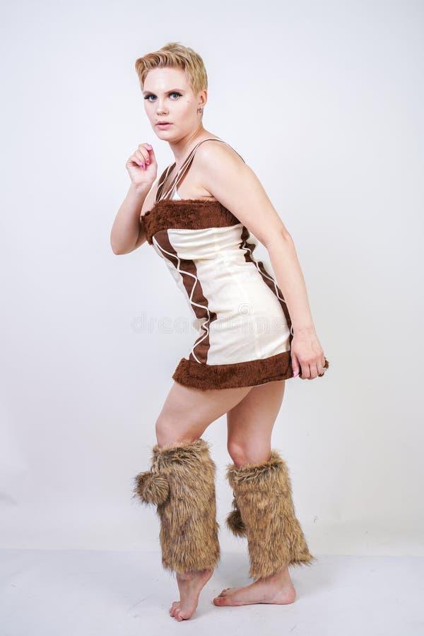 毛皮原始人狂欢节服装的热的正大小妇女白色背景的在演播室 一棕色dre的一个美丽的野蛮女孩 免版税图库摄影