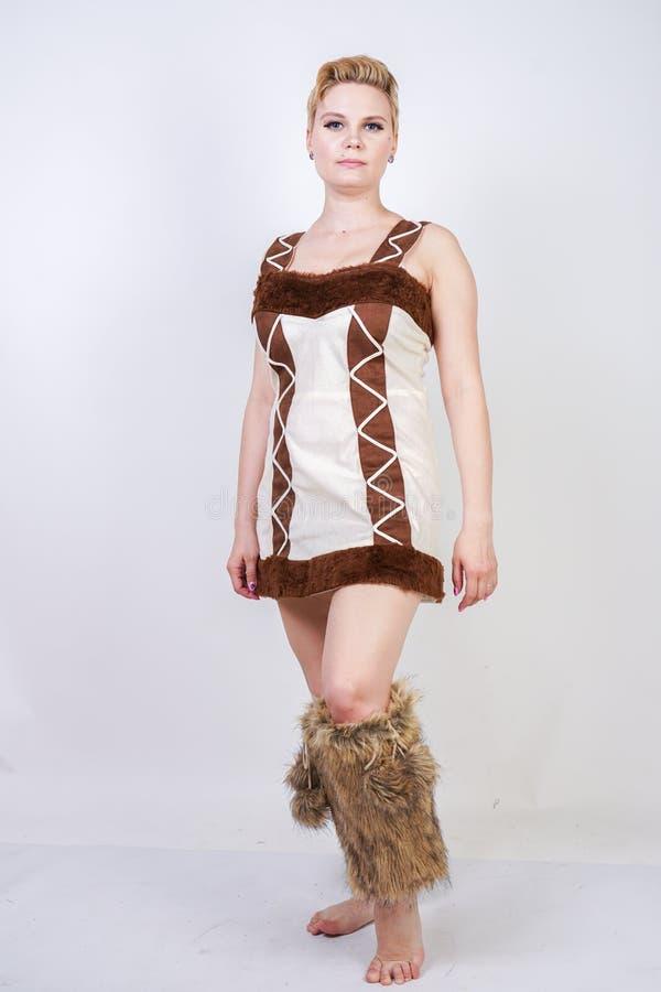 毛皮原始人狂欢节服装的热的正大小妇女白色背景的在演播室 一棕色dre的一个美丽的野蛮女孩 免版税库存图片