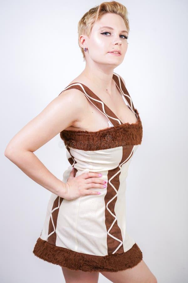 毛皮原始人狂欢节服装的热的正大小妇女白色背景的在演播室 一棕色dre的一个美丽的野蛮女孩 库存照片