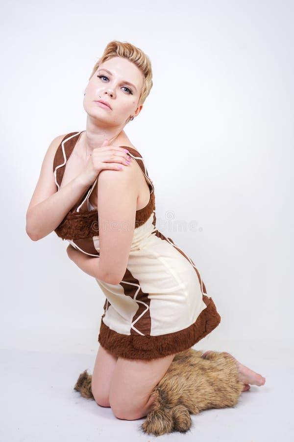 毛皮原始人狂欢节服装的热的正大小妇女白色背景的在演播室 一棕色dre的一个美丽的野蛮女孩 免版税库存照片