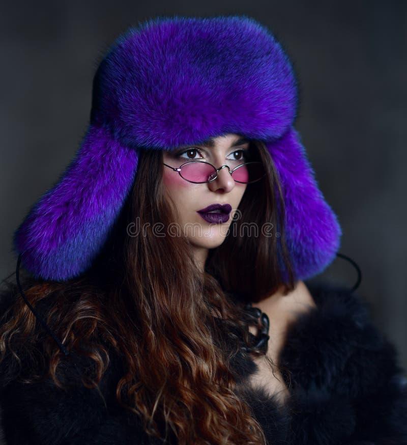 毛皮大衣和蓝色变色蜥蜴帽子的年轻时尚女孩在黑暗的现代桃红色太阳镜 免版税库存图片