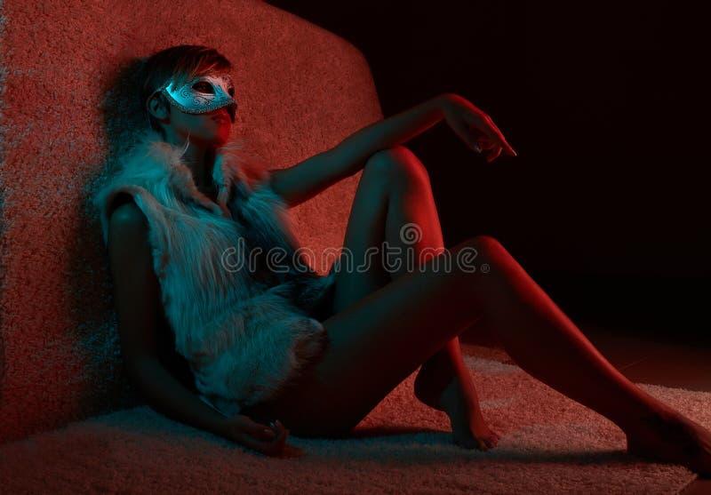 毛皮夹克佩带的面具的性感的女孩 库存图片