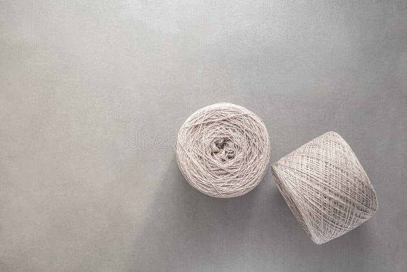 毛纱两个丝球在浅灰色的纸背景的 库存图片